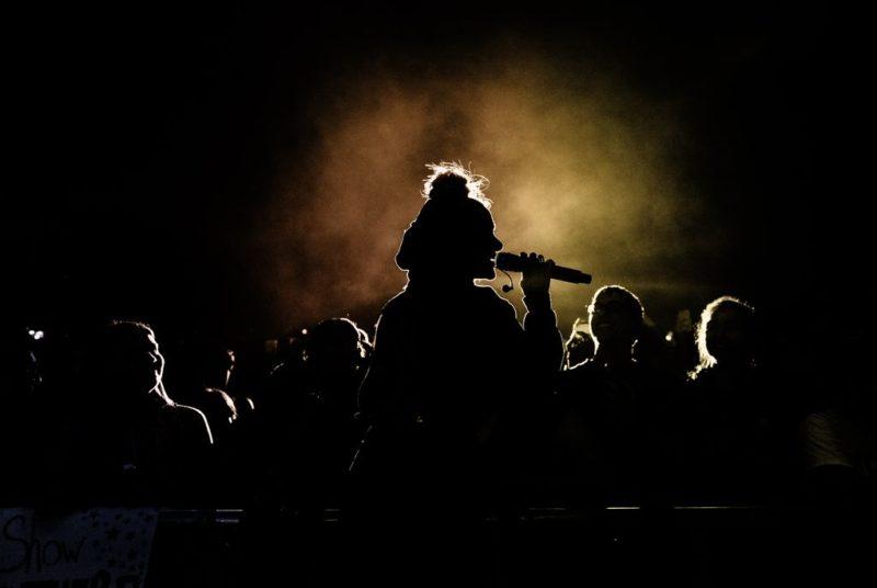 Karaoke Sängerin vor leuchtendem Hintergrund mit jubelnden Fans