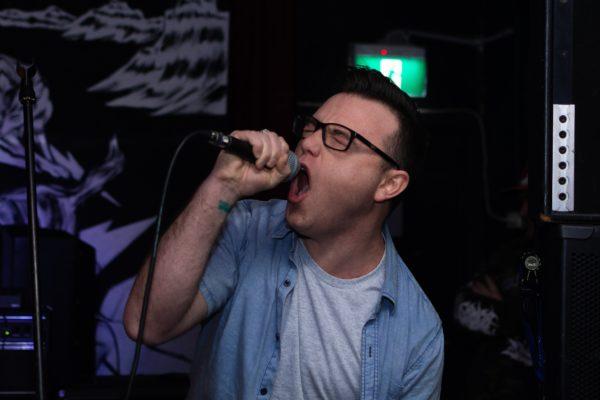 Junger Mann mit Brille, der Karaoke singt
