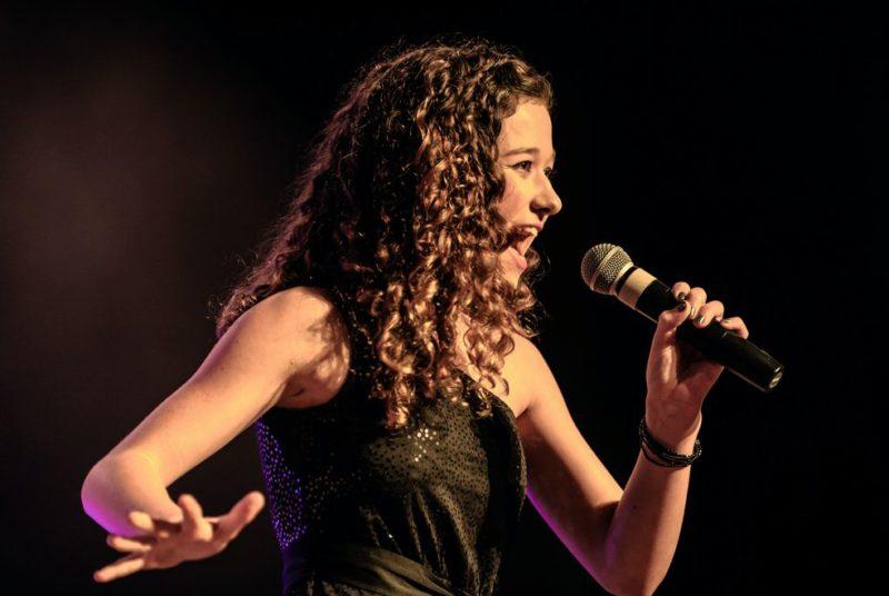 Junge Frau h#lt Mikrofon in der Hand und singt energisch ein Karaoke Lied.