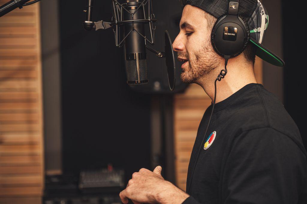 Mann singt a capella in ein Mikrofon und trägt Kopfhörer